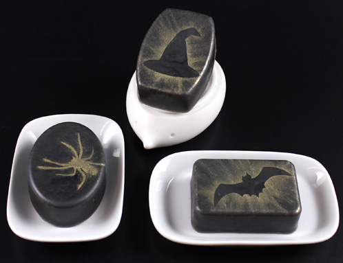 hree bars of Halloween soap. Black bars with glod mica stencil details.
